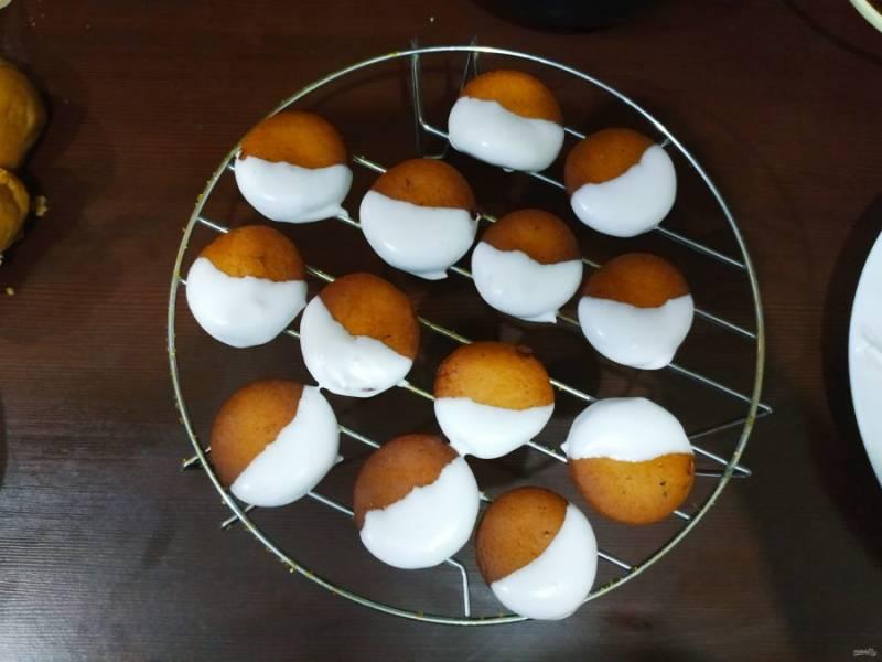 Когда печеньки испекутся, аккуратно, еще горячими окуните до половины в глазурь и отправьте на решетку.