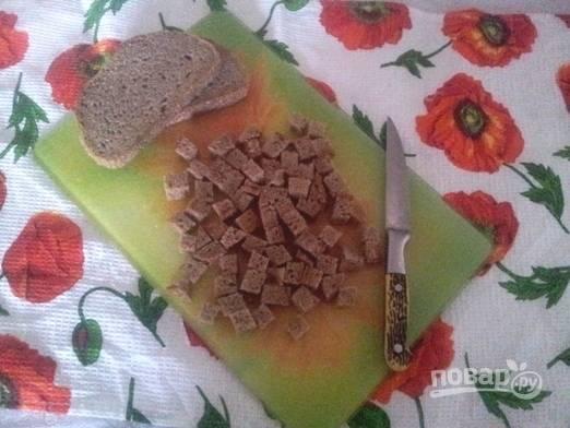 Приготовим домашние сухарики. Для этого хлеб нарезаем небольшими кубиками. Но можно использовать и магазинные сухарики с разными вкусами.