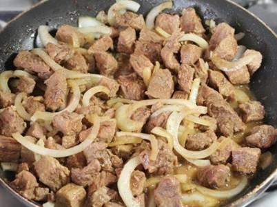 3.  Затем нужно нарезать лук, обжарьте его на сковороде, смазанной растительным маслом, до золотистого цвета. Затем следует добавить чеснок, мясо и обжаривать на сильном огне 5–10 минут до образования на мясе золотистой корочки. Затем — разложить получившуюся смесь по горшочкам, добавить специи и соль по вкусу.