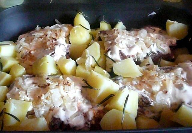 На мясо выкладываем репчатый лук, а по бокам раскладываем картофель вперемешку с веточками розмарина.