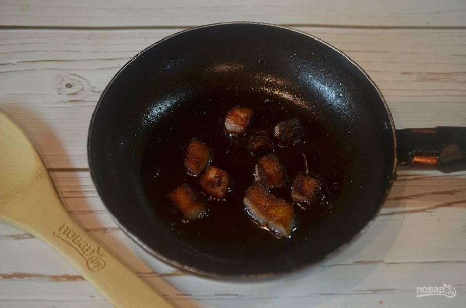 2. На сковороде с 1 ложкой растительного масла хорошо поджарьте нарезанный произвольно жир. Уберите шкварки из сковороды.