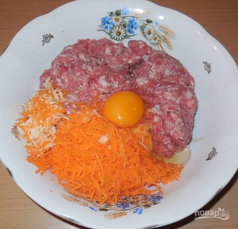 Добавьте морковку и чеснок к фаршу. Вбейте туда же яйцо. Посолите и поперчите.