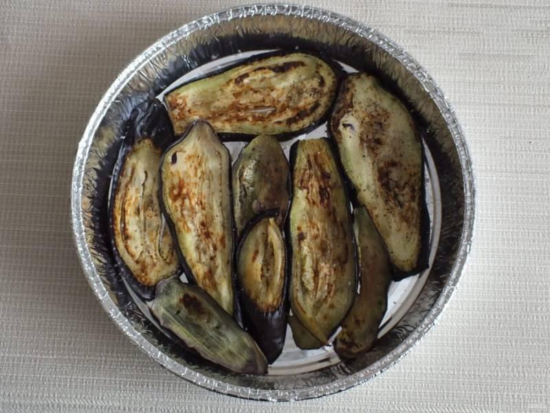 Возьмите форму для запекания и выложите половину обжаренных баклажанов.