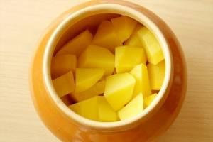 3. Далее - нарезка картофеля. Шинкуем его кубиками среднего размера и выкладываем его в горшочек. По желанию, можно промазывать слои майонезом.