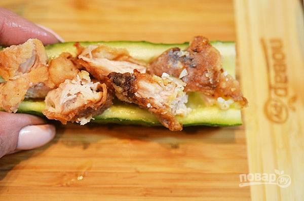 В огурец без сердцевины выложите кусочки курицы.