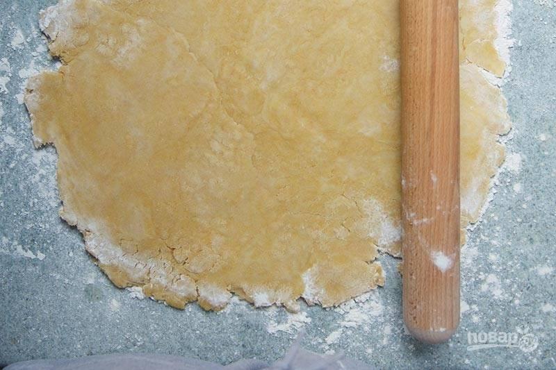 5. Тесто раскатайте, выложите в жаропрочную форму. Застелите пергаментом, сверху всыпьте горох или фасоль (чтобы в процессе оно не поднималось) и отправьте  в разогретую до 200 градусов духовку на 10-12 минут.