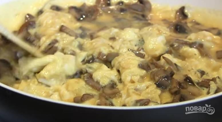 5. Через минуту с помощью лопатки перемешайте грибы с омлетом, накройте крышкой и жарьте до готовности.