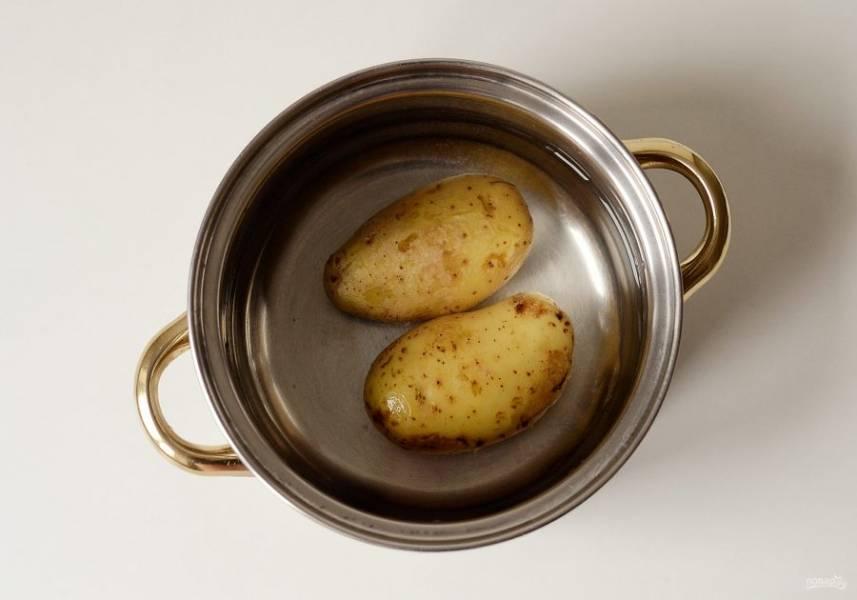 Картофель тщательно помойте. Затем положите в кастрюлю с кипящей подсоленной водой. Варите картошку в мундирах 15-20 минут.