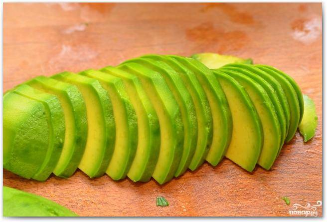 На тонкие ломтики нарезаем очищенный от кожуры авокадо.