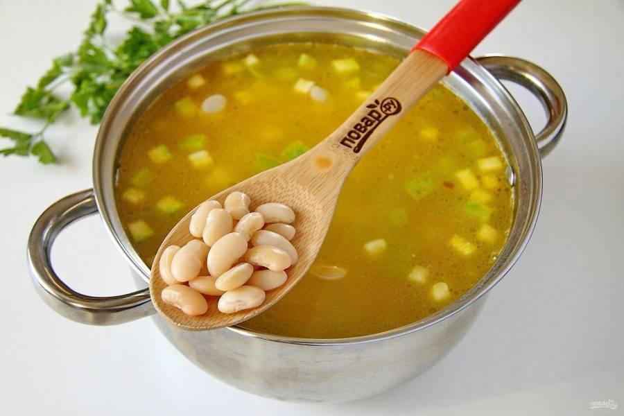 Затем добавьте отваренную фасоль вместе с небольшим количеством отвара. Продолжайте варить суп еще около 10 минут.