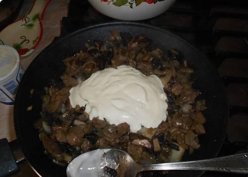 2. Добавляем в середине жарки грибы и мелко нарезанный лук. Солим и приправляем по вкусу, постоянно мешаем и в конце добавляем сливки.