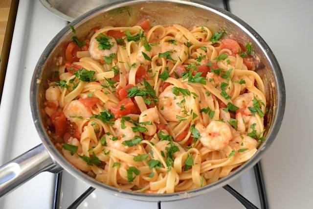 7. Базилик мелко нарезаем, посыпаем готовую пасту с креветками и помидорами. Выкладываем на тарелки и подаем. Приятного аппетита!