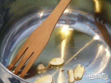 В сотейник влейте небольшое количество растительного масла, желательно оливкового, и разогрейте его на плите. Очистите от шелухи чеснок и раздавите зубчики ножом. Бросьте его в масло и обжарьте две-три минуты, а затем достаньте.