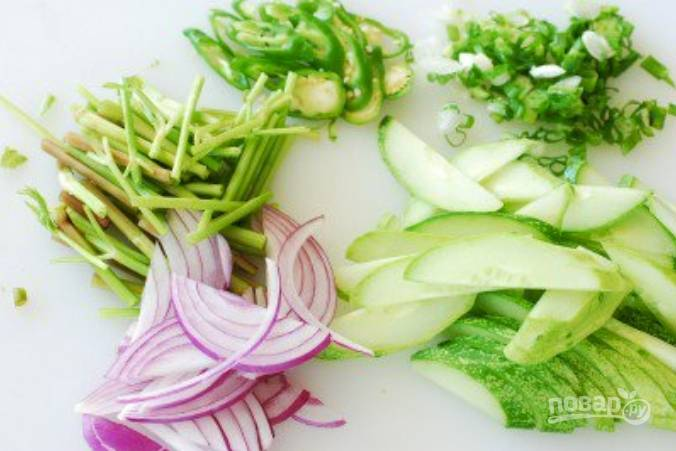 Нарежьте тоненько овощи и измельчите зелень.