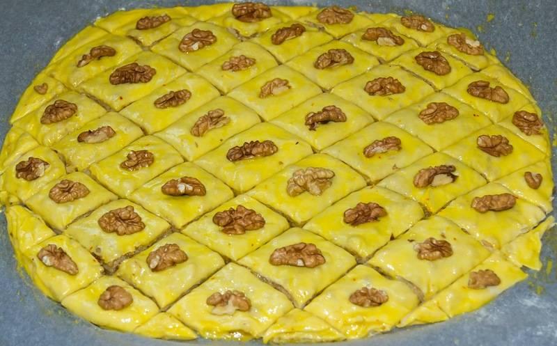 Далее мы разрезаем нашу пахлаву на ромбы и украшаем грецкими орехами. Ставим форму в разогретую до 180 градусов духовку и готовим 35-40 минут.