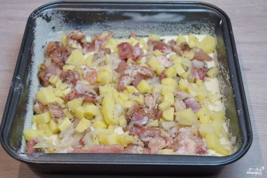 7. В форму влейте 50% теста. Распределите. После выложите картофельно-мясную начинку. Разровняйте.