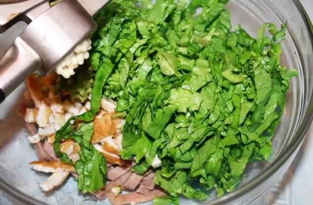 5. Листья салата (можно использовать абсолютно любую зелень, которая есть под рукой) вымыть, просушить и слегка измельчить. Добавить в салатник к языку и омлету. Чеснок очистить и выдавить через пресс.