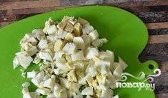 Яйца очистите от скорлупы и пропустите через яйцерезку. Морковь нарежьте кубиками, а помидоры — кольцами. Сыр натрите на крупной тёрке.