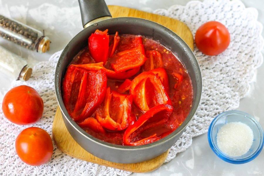 Очистите болгарский перец от семян, срезав крышечки. Промойте овощи и нарежьте четвертинками или пополам. Перелейте томатную массу в казан или ковш, добавьте туда же нарезку перца.