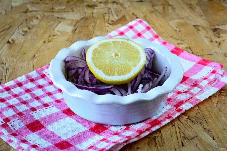 Красный лук почистите и нарежьте полукольцами. Полейте лимонным соком и оставьте мариноваться на 10-15 минут.
