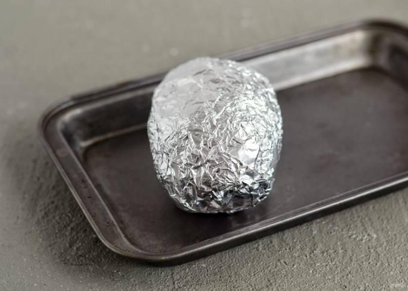 Картофель хорошо промойте, обсушите и заверните в два слоя фольги. Запекайте картошку 1,5 часа в духовке при температуре 200 градусов.
