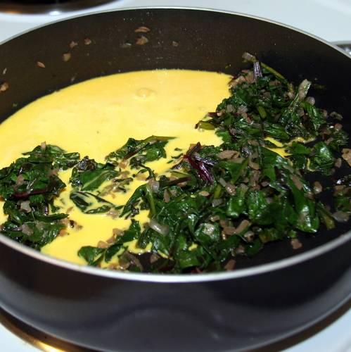 1. В сковороде с толстым дном растопим масло, обжарим на нем лук с измельченной ботвой. Затем добавим сметану и взбитые яйца.