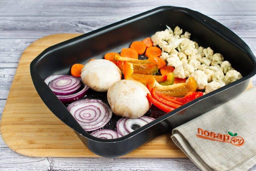Лук нарежьте кольцами, морковь - кружками, перец - полосками. Разложите овощи и грибы на противне, посолите и поперчите по вкусу, полейте растительным маслом.