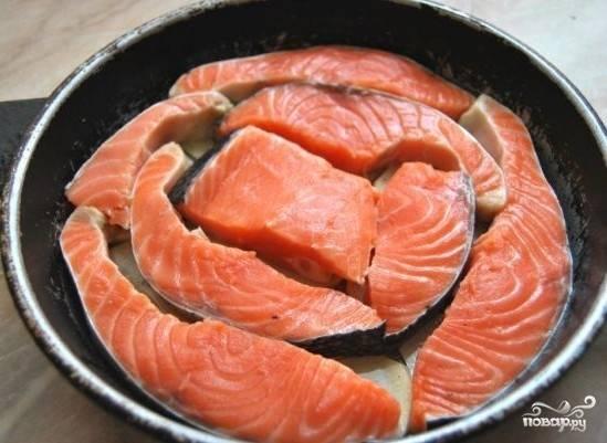 Семгу нарезаем на порционные кусочки и выкладываем на картофель, поливаем рыбу соком половины лимона.