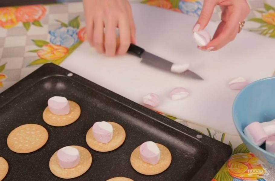 2. Маршмеллоу разрежьте, если они у вас довольно большие, ведь они немного растекутся и поднимутся в духовке. Далее выложите маршмеллоу на печенье и отправьте в разогретую до 180 градусов духовку.