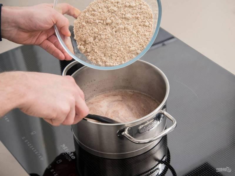 2. Пока займитесь начинкой. В сотейнике доведите до кипения молоко, сахар и корицу. Затем в массу всыпьте измельчённые орехи. Всё перемешайте и остудите.