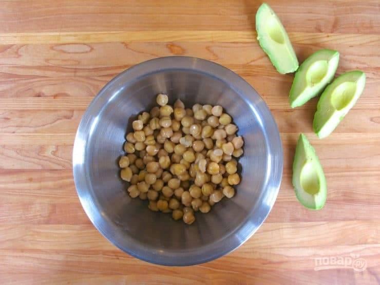 1. В салатницу выложите нут. Авокадо разрежьте, удалите косточку. Затем мякоть вытащите и размягчите вилкой.