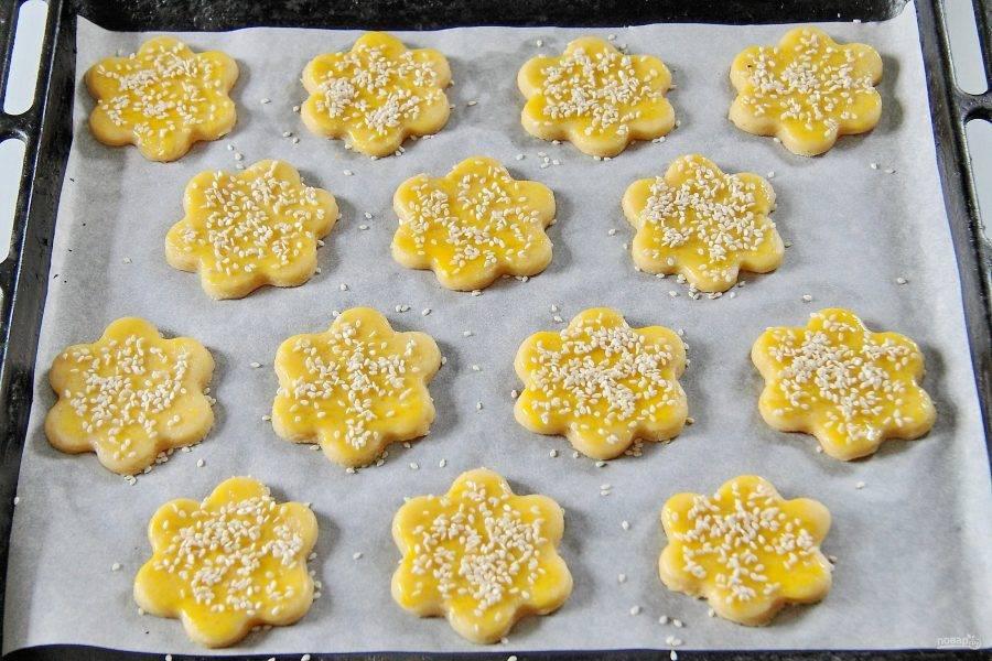 7. Переложите печенье на противень, застеленный пергаментом. Смажьте желтком и посыпьте кунжутом. Выпекайте при 180 градусах около 10 минут.