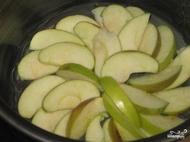 Яблоки порежьте дольками. Смажьте чашу мультиварки сливочным маслом, выложите в неё яблоки.