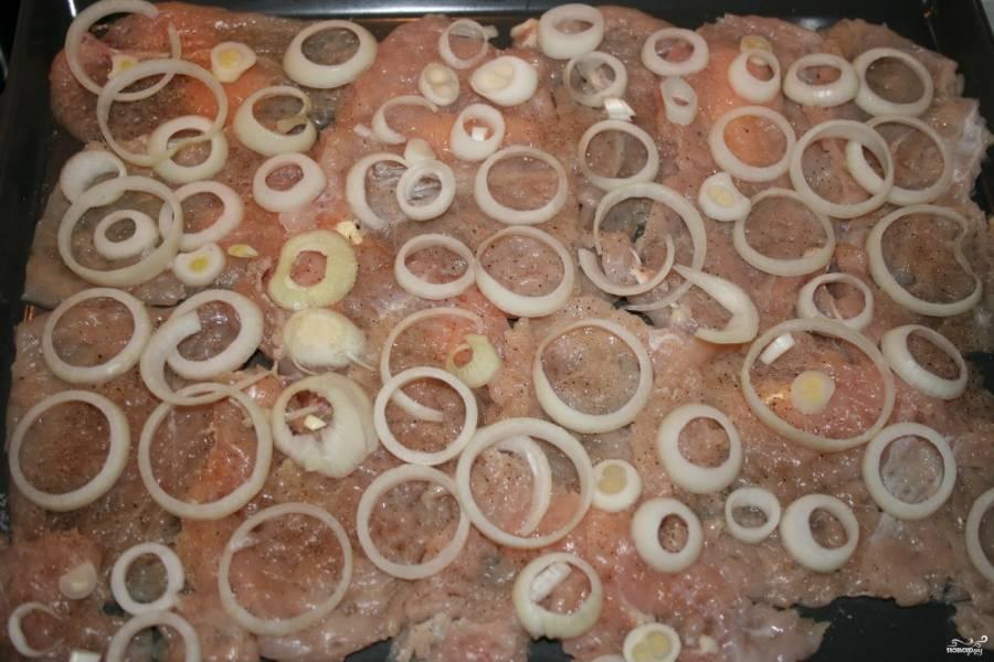 Мясо посолите и поперчите по вкусу, сверху выложите луковые колечки.