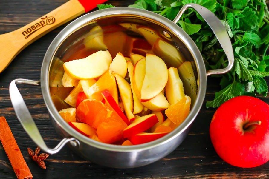 Очистите апельсин от кожуры, разделите на дольки. Каждую дольку очистите от пленки и нарежьте на части, выложите в кастрюлю или казан, ковш. Промойте яблоко в воде, разрежьте его на четыре части и удалите семенные блоки. Нарежьте дольками и высыпьте нарезку в кастрюлю.