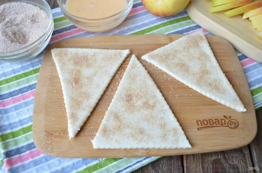 Каждый треугольник смажьте яйцом, посыпьте щедро сахаром с корицей.