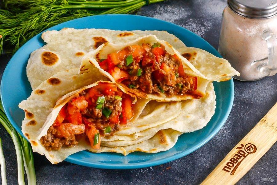 Таким образом обжарьте и остальные заготовки. Выложите их на тарелку и разрежьте пополам. Наполните обе части каждой питы приготовленной начинкой.