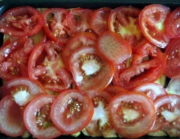 Затем выкладываем помидоры, на них зелень с чесноком. Сверху сделайте сетку из майонеза.
