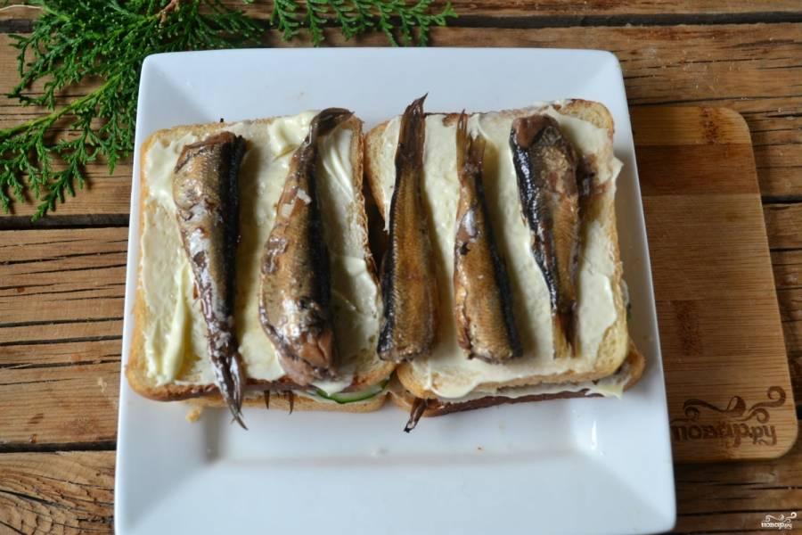 Накройте еще двумя ломтями хлеба, смажьте их майонезом и положите оставшиеся шпроты.