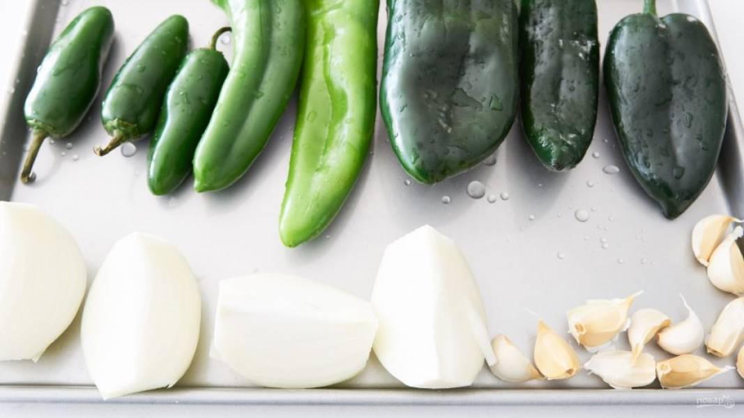1.Помойте перцы и сделайте в них надрезы. Почистите лук и разрежьте его на 4 части. Возьмите чеснок, разделите его на зубчики, но не очищайте от шелухи. Выложите эти ингредиенты на емкость для запекания и поставьте в заранее разогретую до максимума духовку.