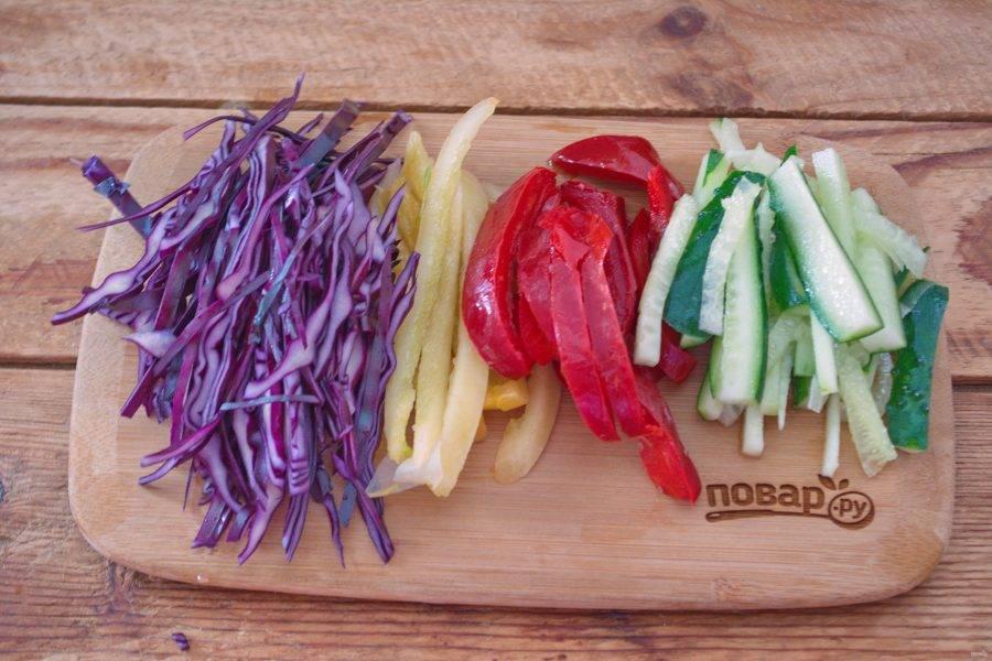 Красную капусту нарежьте соломкой. Свежий огурец нарежьте брусочками. Два вида болгарского перца очистите от семян и нарежьте соломкой.