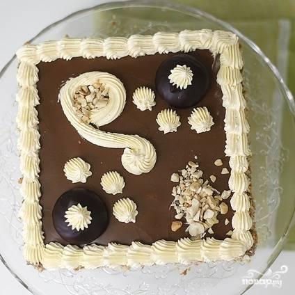 """Верхним будет корж, смазанный помадкой. Бока торта смазываем оставшейся четвертью крема, сверху украшаем торт оставленным белым кремом и орехами. Отправляем торт в холодильник на пару часов, после чего """"Ленинградский"""" торт можно подавать к столу. Приятного аппетита!"""