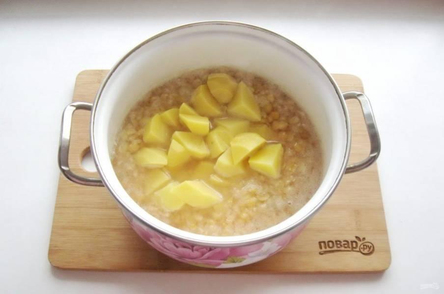 Когда горох начнет развариваться, добавьте в суп нарезанный картофель.