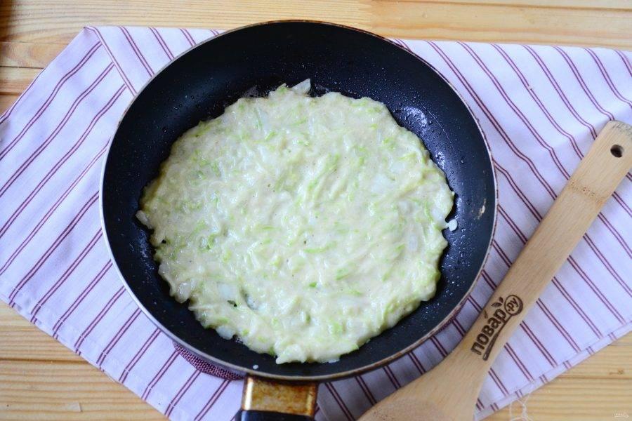 На сковороде разогрейте 1 ст. ложку растительного масла. Затем на середину положите примерно 4 ст. ложки кабачковой массы и быстро распределите ложкой по сковороде, чтобы получился нетолстый блин диаметром с тарелку. Жарьте с двух сторон 2-3 минуты до золотистого цвета.