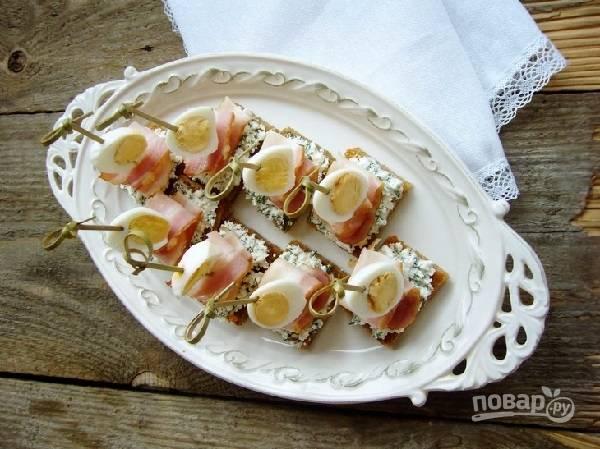 6. Хлеб смажьте сыром с зеленью. С помощью шпажки закрепите на нем ломтик бекона и половинку яйца. Вот такая красота! Приятного аппетита!