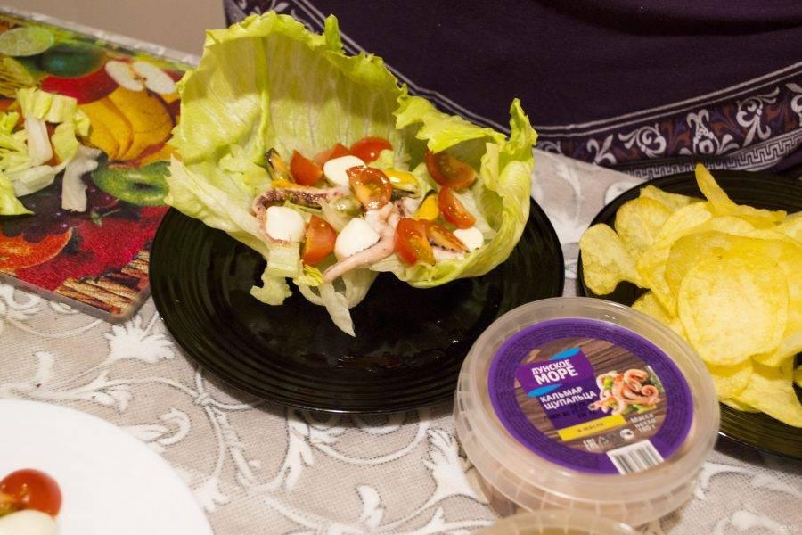 Салат мы будем собирать порционно. Выкладываем наш красивый лист салата с одной стороны тарелки и на него (как на фото) слоями начинаем выкладывать остальные ингредиенты, создаем небольшую подушку из полосок салата, аккуратно укладываем помидоры черри, сыр и наши морепродукты. Морепродукты я лично не режу, потому что считаю, что если их рвать, то получается вкуснее и красивее и проще украшать. Не забываем немножко солить и перчить каждый слой (без фанатизма)!