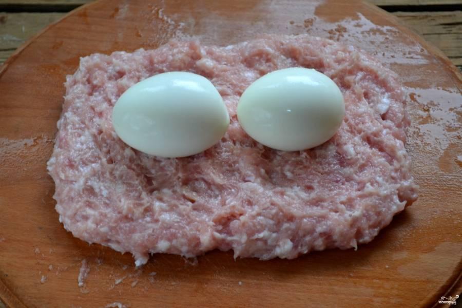 Разделочную доску смочите водой, расложите на ней фарш пластом толщиной примерно 1 см. Сверху положите 2 сваренных вкрутую яйца.