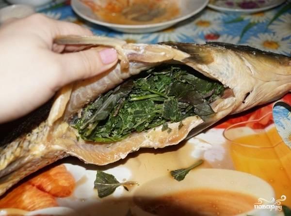 2. Когда рыбка немного пропиталась, включите духовку и оставьте разогреваться до 180 градусов. Зелень (а я использую в рецепт приготовления сазана в сметане укроп, базилик, петрушку) вымойте и поместите в брюшка. Кстати, вполне можно взять и замороженную зелень. По желанию также внутрь можно поместить ломтики лимона.