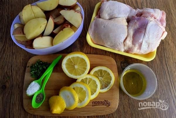 Подготовьте необходимые продукты. Картофель тщательно помойте, нарежьте на 4 части. Бедра помойте и осушите бумажными полотенцами. Половину лимона нарежьте на кружки, из второй половины выжмите сок.