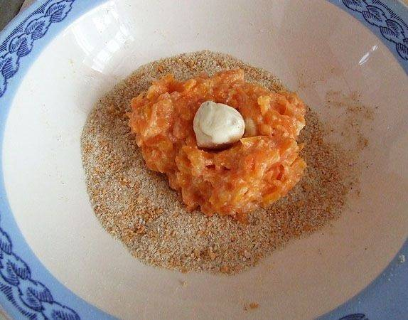 4. В тарелку насыпать панировочные сухарики. Параллельно поставить на огонь сковороду с растительным маслом разогреваться. Небольшую часть морковного фарша выложить в сухари. Можно сделать морковные котлеты на скорую руку в домашних условиях с небольшим сюрпризом. Это может быть чайная ложка плавленого сыра, зелень или орешек, например.